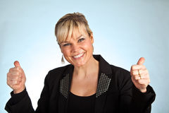 Studio portrait of a cute blond girl with thumbs up Royalty Free Stock Image