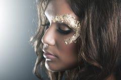 Studio portrait with dark skin and golden makeup Stock Image