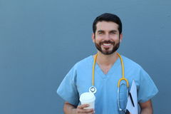Studio Portrait Of Doctor Leaning Against Blue Background Royalty Free Stock Photos