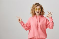 Studio portrait of emotive happy feminine woman with curly hair, wearing casual hoodie and sunglasses showing ok sign. And pointing left with index finger Royalty Free Stock Image