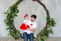 Studio portrait of a father and baby daughter on a rope swing. St. Valentine`s Day. Studio portrait of a father and baby daughter on a rope swing. St. Valentine Stock Images