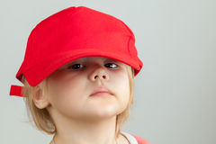 Studio portrait of funny baby girl in big red baseball cap Stock Photos