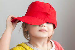 Studio portrait of funny baby girl in red baseball cap. Over gray wall background Royalty Free Stock Photos