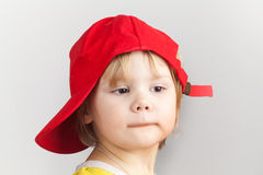Studio portrait of funny baby girl in red baseball cap Royalty Free Stock Photo