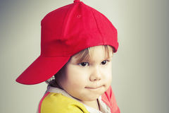 Studio portrait of funny baby girl in red baseball cap Royalty Free Stock Image