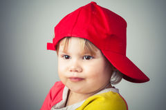 Studio portrait of funny girl in red baseball cap Royalty Free Stock Photos