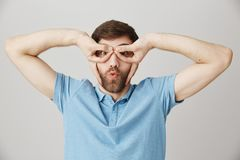 Studio portrait of funny joyful caucasian guy making goggles over eyes with hands, folding lips as if flying on airplane. Standing over gray background. Man royalty free stock photos