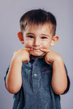 Studio portrait of a funny little boy crummy and stretching his fingers in the mouth in a smile Royalty Free Stock Images