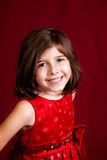 Studio Portrait of a Girl on Red Backdrop. A studio portrait of a cute, smiling girl on a deep red backdrop Royalty Free Stock Photo