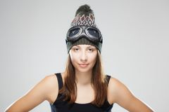 Girl with hat and goggles. Studio portrait of a girl wearing a winter kneeted hat with goggles Stock Image