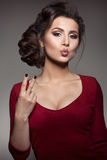 Studio portrait of gorgeous brunette girl gesturing peace sign by fingers and sending air kiss at camera. Woman wearing red dress Stock Image