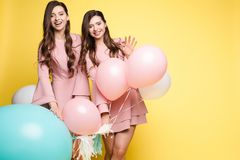 Cute brunette twins in pink dresses over yellow background. Studio portrait of gorgeous brunette twins posing in trendy elegant pink dresses. Stylish outlooks royalty free stock photos