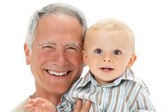Studio Portrait Of Grandfather Holding Grandson Stock Photo