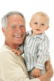 Studio Portrait Of Grandfather Holding Grandson Stock Images