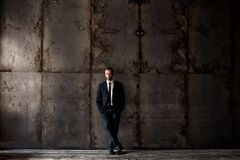 Handsome man wearing black suit on a grunge background. Studio portrait of a handsome man wearing black suit on a grunge background royalty free stock photos