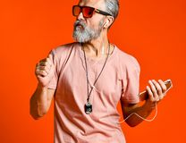 Studio portrait of handsome senior man with gray beard and headphones. royalty free stock photos