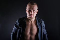 Studio portrait of handsome sexy sporty young man. Muscular man with naked torso wearing black shirt Royalty Free Stock Photos