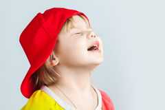 Studio portrait of happy baby girl in red baseball cap Royalty Free Stock Photography