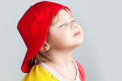 Studio portrait of happy girl in red baseball cap Royalty Free Stock Images