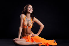 Smiling oriental dancer in orange costume. Studio portrait of happy oriental dancer in orange costume Royalty Free Stock Photo