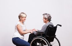Studio portrait of a senior women in wheelchair. Studio portrait of a happy senior women in wheelchair, holding hands royalty free stock photography