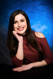 In studio portrait of high school senior girl in red shoulder top and blue background Stock Photo