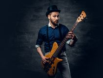 Portrait of the hipster bass player dressed in cylinder hat. Studio portrait of the hipster bass player dressed in cylinder hat Stock Photos