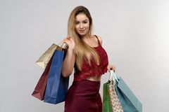 Studio portrait on isolated background of a young woman with long hair. She holds in two hands color packages and shopping bags stock photo