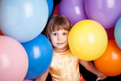 Studio portrait of little blond girl with colorful balloons Stock Photography