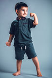 Studio portrait of a little boy posing, showing muscles. Studio portrait of a cute little boy posing on a gray background with joy and a smile royalty free stock photo
