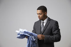 Studio Portrait Of Male Fashion Buyer Looking At Shirts Royalty Free Stock Images