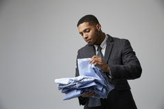 Studio Portrait Of Male Fashion Buyer Looking At Shirts Stock Photography