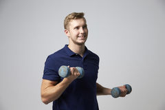 Studio Portrait Of Male Sports Coach Holding Weights Stock Photo