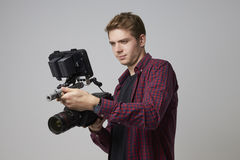 Studio Portrait Of Male Videographer With Film Camera Royalty Free Stock Photos