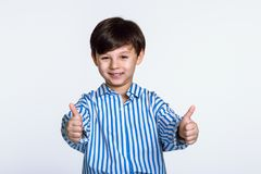Studio portrait of a man child holding two hands with thumbs up. Shot Stock Photo