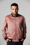 Studio Portrait Of Man Standing Against Grey Background Stock Photo