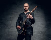 Studio portrait of a man in traditional Celtic clothes playing on mandolin. Studio portrait of a man in traditional Celtic clothes playing on mandolin over grey Stock Photography