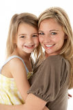 Studio Portrait Of Mother Hugging Young Daughter Stock Images
