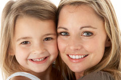 Studio Portrait Of Mother Hugging Young Daughter Stock Photography