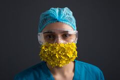 Free Studio Portrait Of A Girl In A Medical Surgical Suit, Goggles And A Medical Protective Mask With Yellow Flowers. On A Gray Royalty Free Stock Photo - 176176915