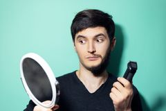 Free Studio Portrait Of Young Surprised Man With Half Shaved Face, Looking In Mirror Holding Electric Shaver Trimmer On Background. Stock Photography - 168547602