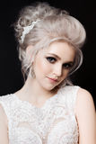 Studio portrait of pretty smiling girl wearing white lace dress with stylish haircut, perfect evening make up, long eyelashes. Wom Stock Photography