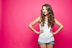 Pretty girl with curly hairstyle holding hands on waist and smiling.