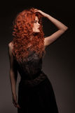 Redhead woman with long hair. Studio portrait of redhead woman with long hair on dark background Stock Photography