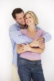 Studio Portrait Of Romantic Couple Embracing Against White Backg Stock Photo