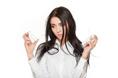 Sad woman holding nasal spay and medicament. Studio portrait of sad brunette woman in shirt holding nasal spay and medicament in hands and posing. Concept of Stock Images