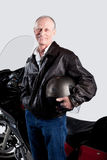 Studio portrait of a senior man standing by his motorcycle isolated on white. Stock Photo