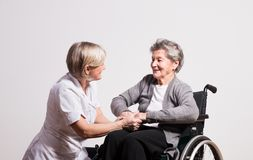 Studio portrait of a senior nurse and an elderly woman in wheelchair. Studio portrait of a senior nurse and an elderly patient in wheelchair. Two women talking royalty free stock image