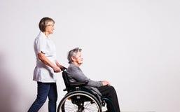 Studio portrait of a senior woman in wheelchair and a nurse. stock photo