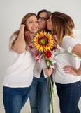 Mother and two twin sisters enjoy in very funny attitude with a big sunflower in their hands stock image